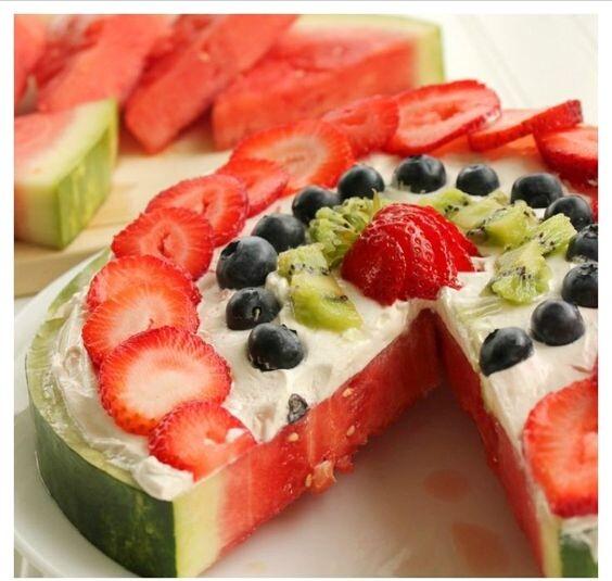 Anguria guarnita con panna e frutta fresca