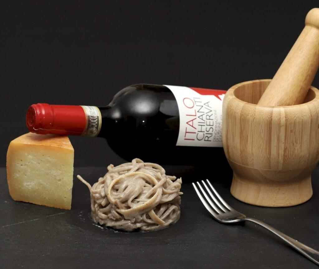 una porzione di pasta cacio e pepe risottata accompagnata con con vino chianti