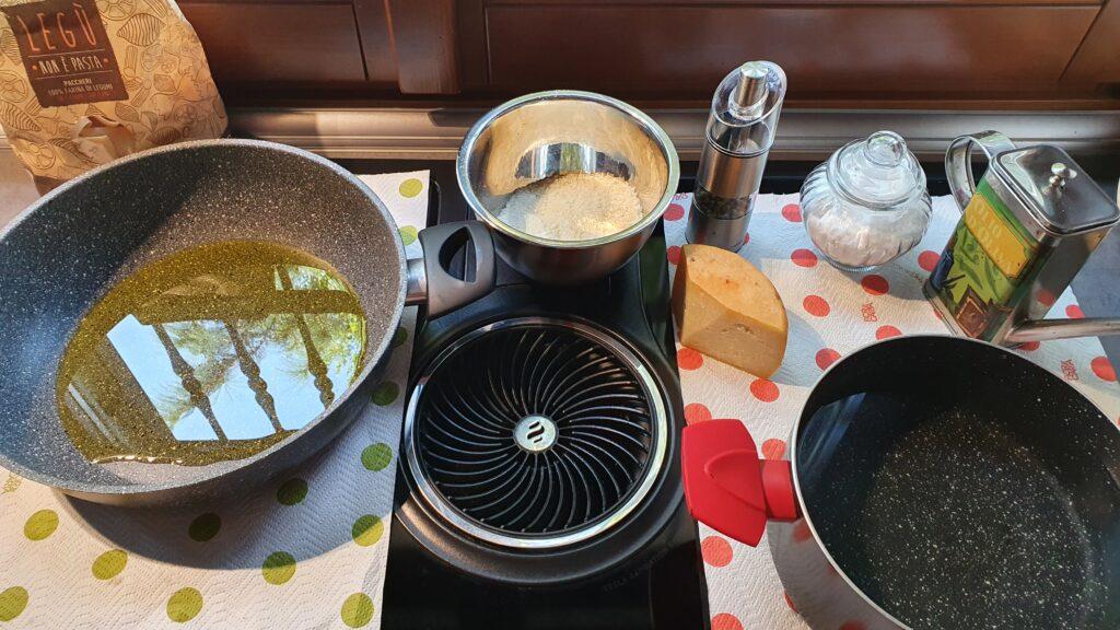 tutti gli ingredienti pronti (pasta, acqua salata bollente, padella grande con olio d'oliva,pecorino e pepe) per  fare una pasta cacio  e pepe risottata