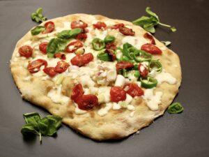 pizza in teglia con mozzarella.cipollotti e pomodorini confit